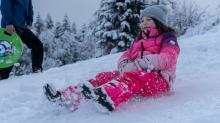 Kinder rodeln mit ihren Schneerutschern