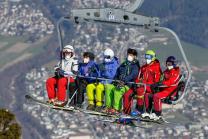 Skifahrer mit Maske am Sessellift